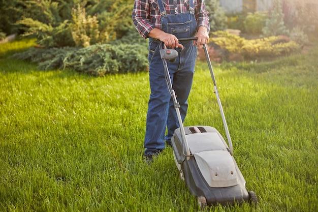 草刈り機で芝生を動かす勤勉な庭師のトリミングされた写真