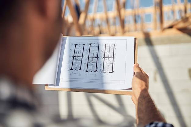建設現場で建物のホワイトプリントを使用してクリップボードを保持している男性のトリミングされた写真