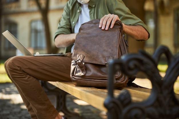 Обрезанное фото мужчины в повседневной одежде, который что-то ищет в кожаной сумке