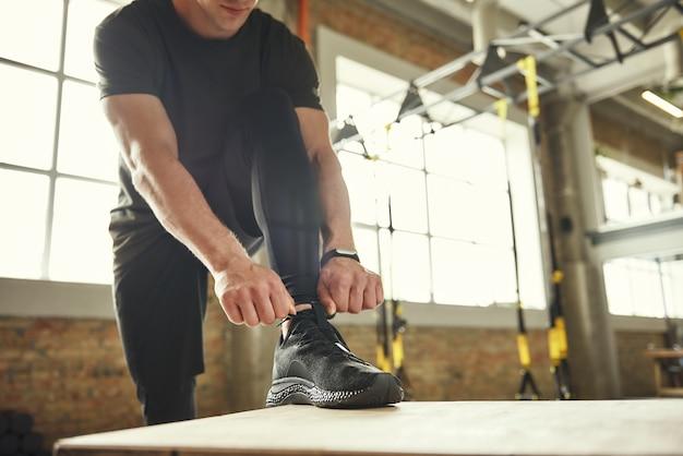 ジムで運動中に靴ひもを結ぶスポーツウェアの男性のトリミングされた写真。