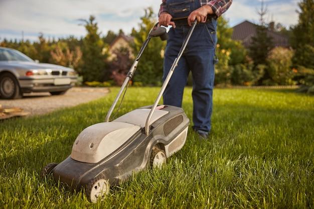 ジーンズのジャンプスーツを着て、芝刈り中に草刈り機を押す男性のトリミング写真