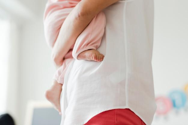 赤ちゃんを抱いている親のトリミングされた写真