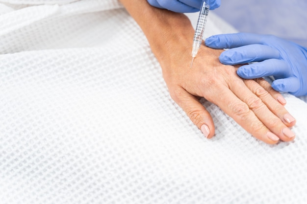 와플 목욕 가운을 입은 환자가 손에 진피 필러를 주입하는 사진