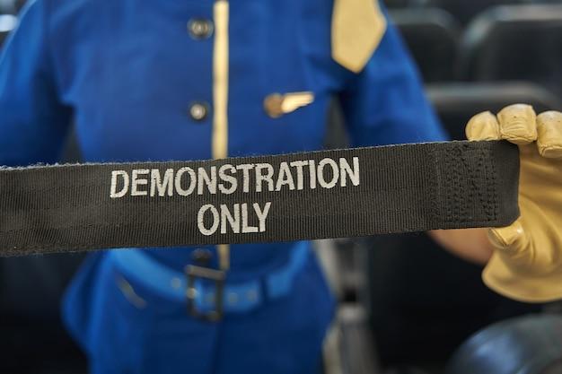 Обрезанное фото ремня безопасности для демонстрации правил техники безопасности в руках профессиональной стюардессы