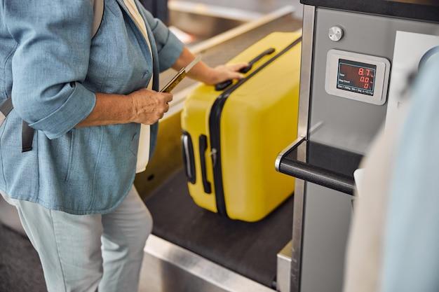 ベルトコンベアにバッグを置いている白人女性のシニア乗客のトリミングされた写真