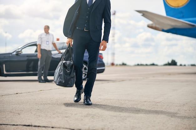 飛行機の近くを歩いている黒いバッグを運ぶ成功した実業家のトリミングされた写真