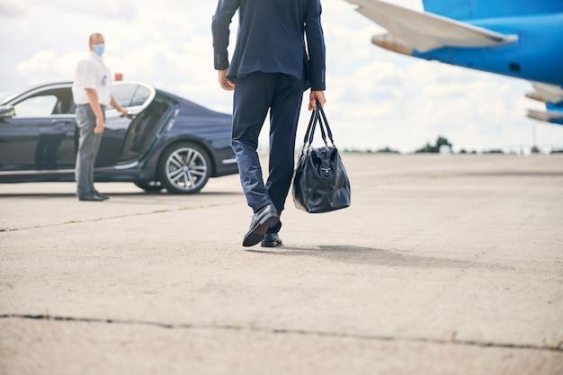 タクシーに向かってダッフルバッグを運ぶ成功した実業家のトリミングされた写真