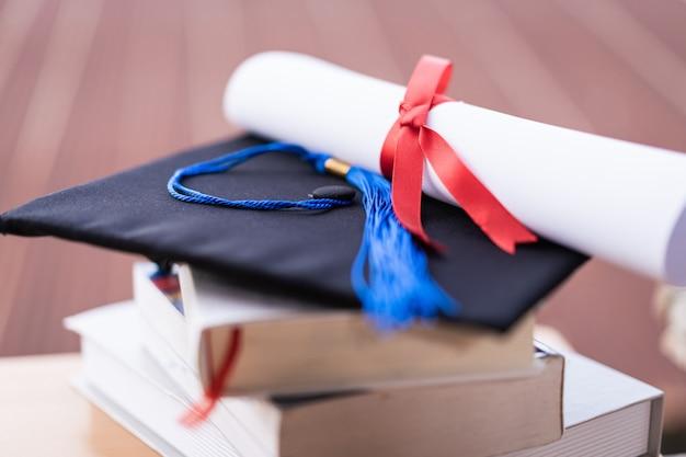 Обрезанное фото выпускной шляпы университета и свидетельство о дипломе на столе