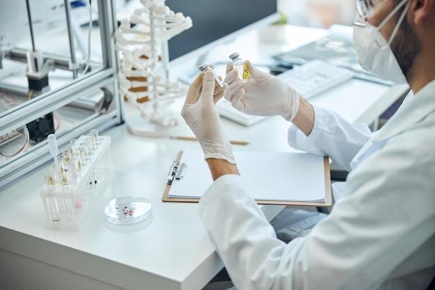 Обрезанное фото вирусолога в лабораторном халате и латексных перчатках, исследующего вакцины от коронавируса