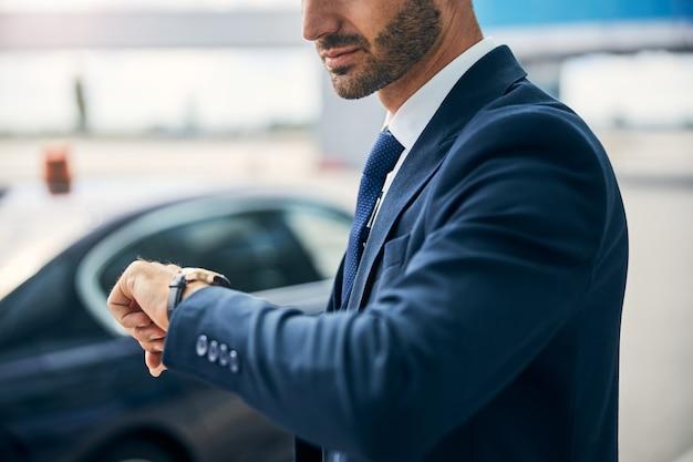 Обрезанное фото хорошо одетого мужчины, поднимающего руку, чтобы проверить время на своих наручных часах.