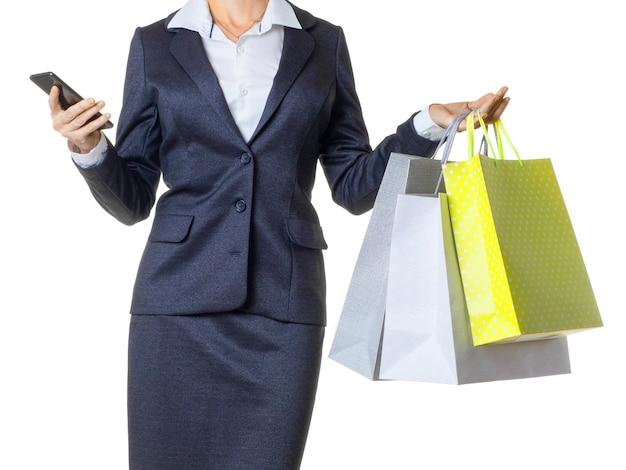 白で隔離のスマートフォンを使用して買い物袋を持つ女性のトリミングされた写真。買い物中毒の概念。