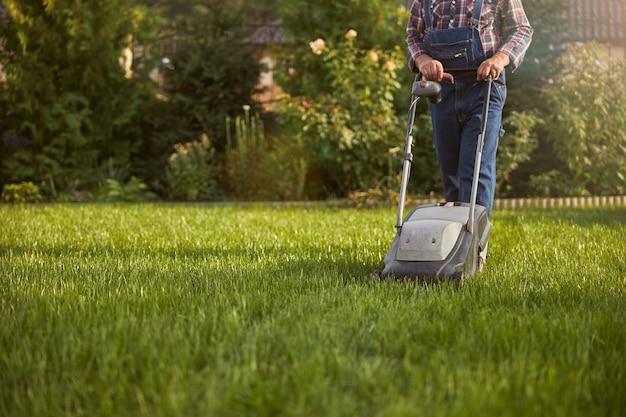 芝刈り機で芝生を動かす働く男性のトリミングされた写真