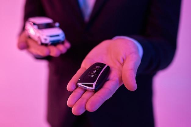 네온 핑크에 고립 된 그의 손바닥에 모델 자동차를 들고 검은 양복과 흰 셔츠에 젊은 매력적인 사업가의 자른 사진