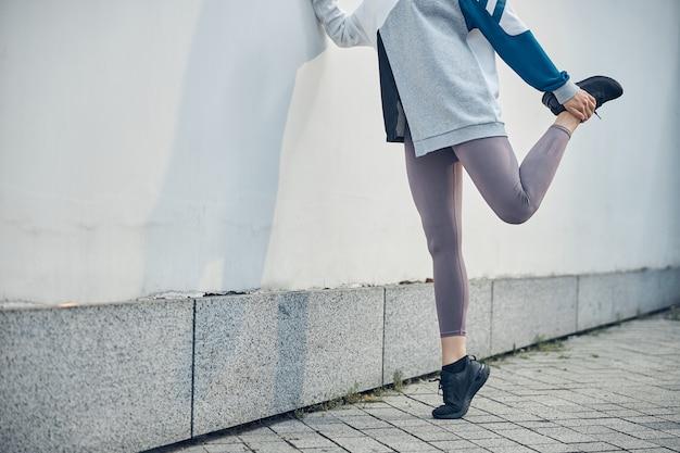 ストレッチ運動中に左足を曲げている若い女性アスリートのトリミングされた写真