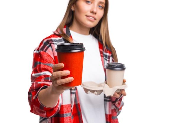 2杯のコーヒーのテイクアウトのうちの1杯をあなたに与える若い女性のトリミングされた写真。
