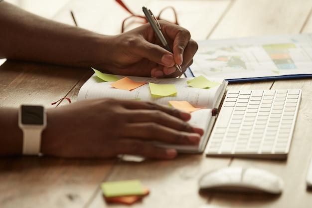 집에서 원격으로 일하는 동안 메모를 하는 아프리카계 미국인 사업가의 자른 사진