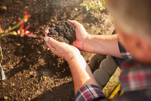彼の庭に2握りの土を持つ老人のトリミングされた写真