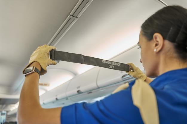Обрезанное фото стюардессы, демонстрирующей пристегивание ремня безопасности во время инструктажа по безопасности в полете.