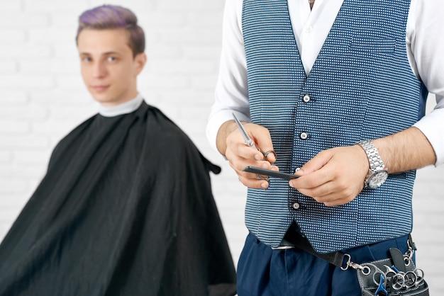 Подрезанное фото парикмахера держит гребень и ножницы, стоящие перед клиентом.