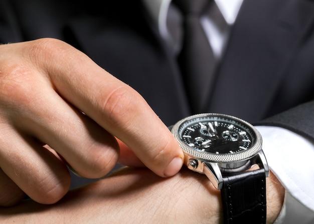 전경에 손목 시계가 있는 사업가의 자른 사진