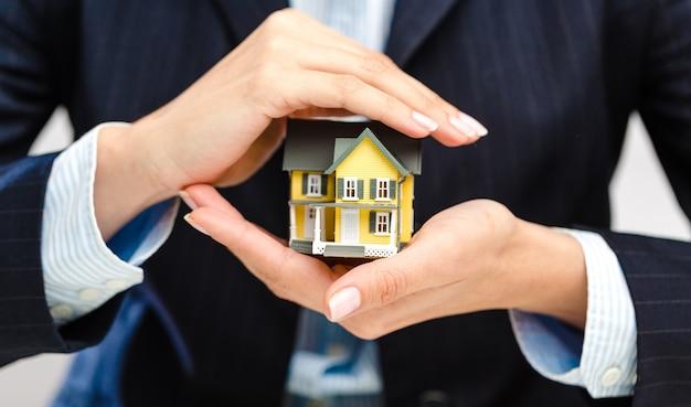 黄色い家のモックを手に持っている実業家のトリミングされた写真