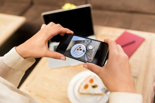スタイリッシュなカフェに座って、携帯電話で食べ物を撮影する帽子をかぶった白人女性のトリミングされた写真