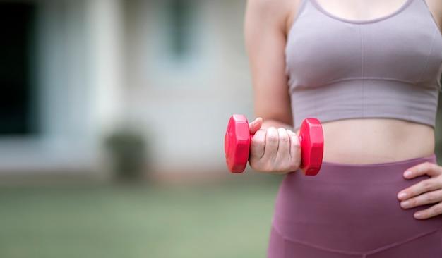 赤いダンベルを屋外で白人女性のトレーニングの写真をトリミングしました。コピースペース。