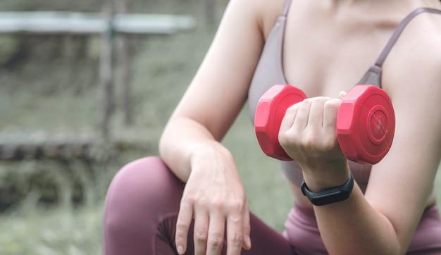 赤いダンベルを屋外で白人女性のトレーニングの写真をトリミングしました。