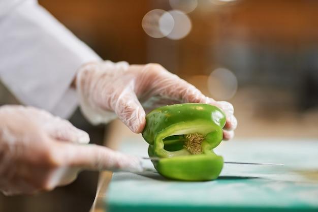 ナイフを持ってピーマンを切るシェフの手のトリミングされた写真