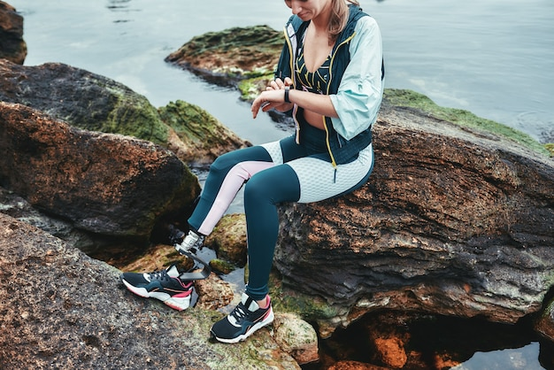 Обрезанное фото женщины-спортсмена-инвалида в спортивной одежде с результатами проверки протеза ноги