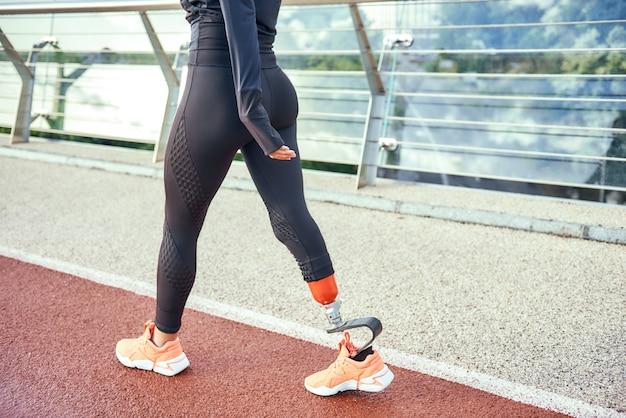 Обрезанное фото женщины-спортсмена с протезом ноги в спортивной одежде, идущей по мосту