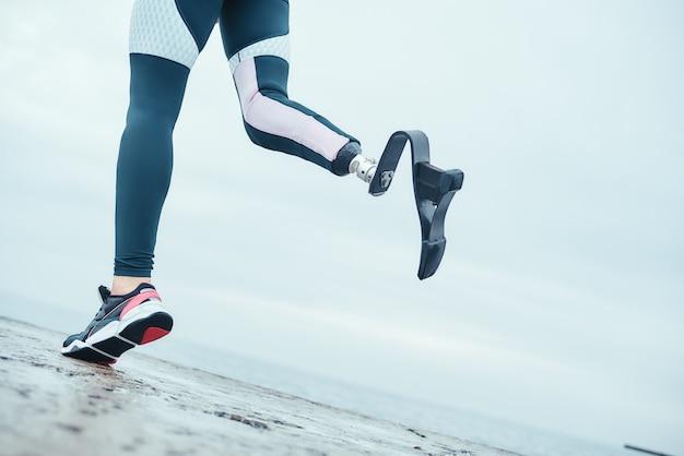 スポーツウェアのバイオニック脚を持つ障害者の女性のトリミングされた写真は、朝のビーチで実行されています