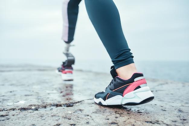 ビーチで走っているバイオニック脚を持つスポーツウェアの障害のある若い女性のトリミングされた写真