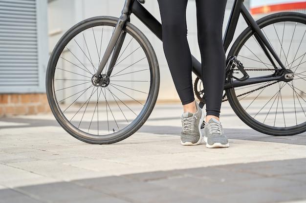 자전거 근처에 서 있는 운동화와 검은색 레깅스를 입은 여성의 자른 사진. 스포츠 및 라이프 스타일 개념