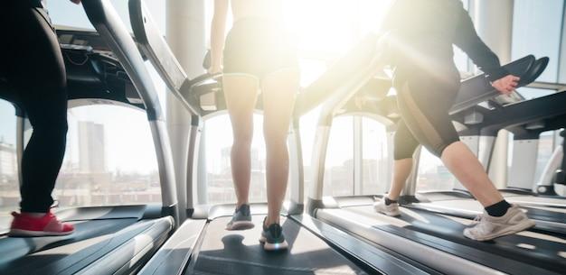 창에 대해 체육관에서 러닝 머신에서 실행되는 운동복과 운동화의 여성 다리 자른 사진