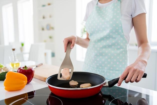 Обрезанное фото хозяйки руки держат сковородку, проверяя состояние мяса готовить вкусный ужин подготовка семейный праздник встреча белый свет кухня в помещении