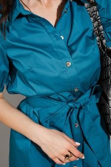 青いドレスに立って黒いバッグを持っている女性のトリミングされた写真。ファッション。ショッピング。夏のコンセプト