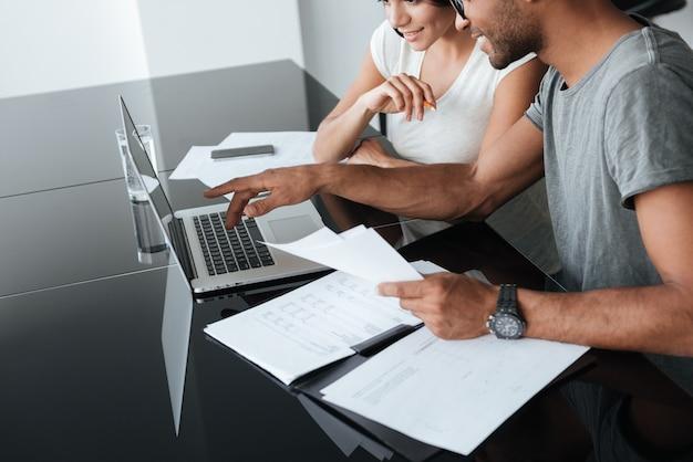 Обрезанное фото влюбленной молодой пары, использующей ноутбук и анализирующей свои финансы с документами.