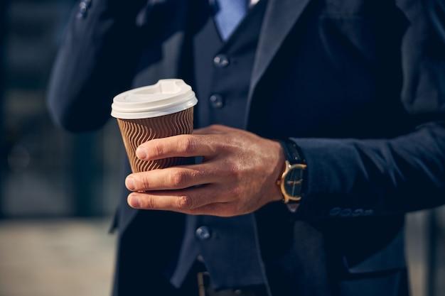 커피를 마시는 손에 시계가있는 공식 옷을 입은 남자의 자른 사진