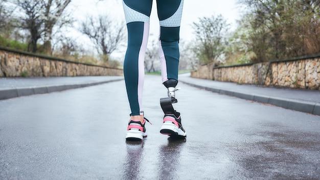 Обрезанное фото женщины-спортсмена-инвалида в спортивной одежде с протезом ноги, стоящей на открытом воздухе