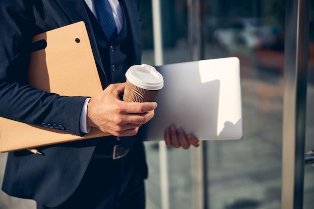 커피와 폴더를 손에 들고 따뜻한 날씨에 밖에 머무르는 사람의 자른 사진