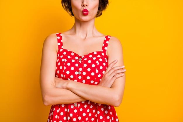Обрезанное фото симпатичной девичьей дамы, скрестив руки, скрыть выражение лица, посылать только пухлые губы, воздушные поцелуи, носить ретро-стиль, красно-белое платье в пунктирную точку, изолированное желтой стене