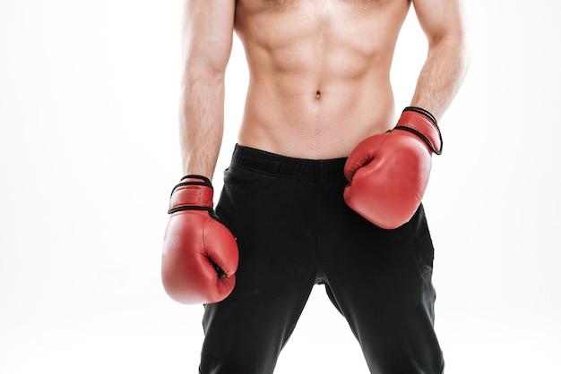Обрезанное фото боксера сильного красивого человека, стоящего над белой стеной.