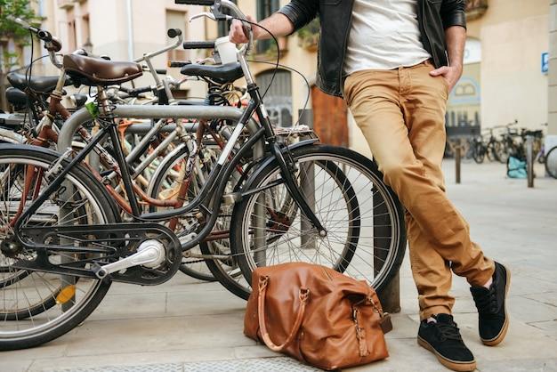 자전거 주차장 근처의 도시 거리에 가죽 가방 서있는 캐주얼웨어의 세련된 성인 남자의 자른 사진
