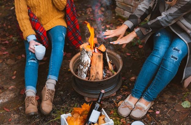 Обрезанное фото трех лучших подруг, сидящих у костра в повседневной одежде, согревающихся и общающихся, с кружками с горячими напитками и счастливых быть вместе на улице холодным осенним вечером
