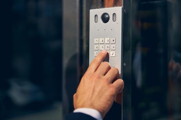 비즈니스 센터의 문을 열 수있는 버튼이있는 특수 장치를 터치하는 자른 사진