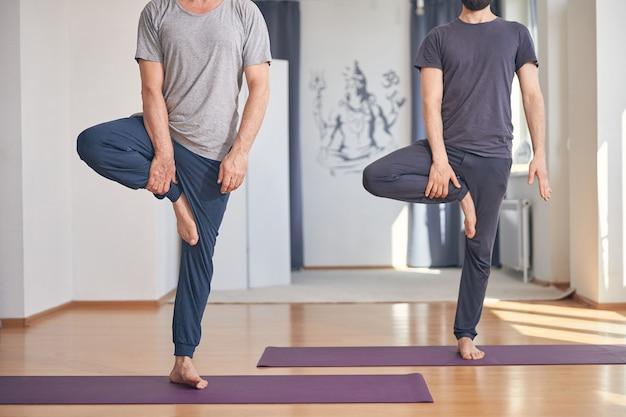 체육관에서 균형 운동을 수행하는 운동복에 두 맨발 남자의 자른 사진