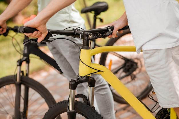 自転車が隣り合って立っている2人の白人の自転車ライダーのトリミングされた写真