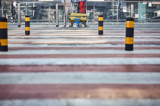 얼룩말 교차점 앞에서 수하물 카트와 함께 서있는 두 노인의 자른 사진