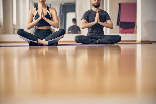 床に足を組んで座っている手を握りしめた2人のスポーティな人々のトリミングされた写真